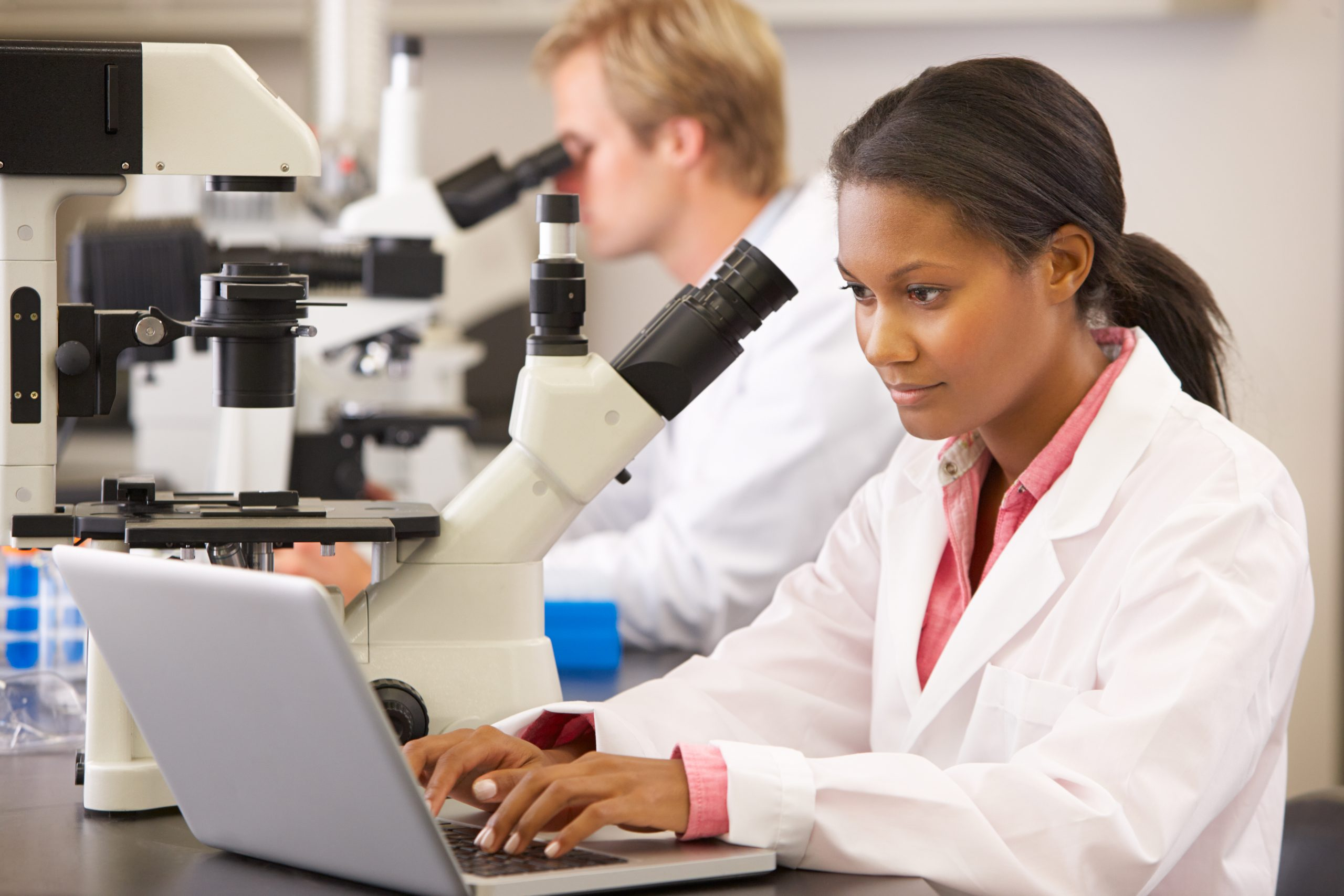 Woman in white lab coat looks into microscope